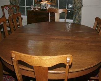 NICE OAK ROUND TABLE WITH 6 LEAVES TO SEAT 12+.  LEAVES HAVE THEIR WOODEN STORAGE  CASE
