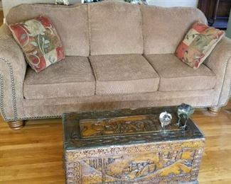 Brown velvet sofa with head to head nail trim. Chinese camphor wood chest with glass top