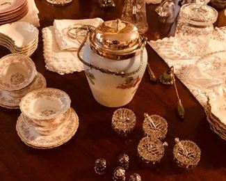A table full of interesting items. Salts with sterling shakers and spoons. Limoges ramekins. Hand painted Victorian biscuit tin.