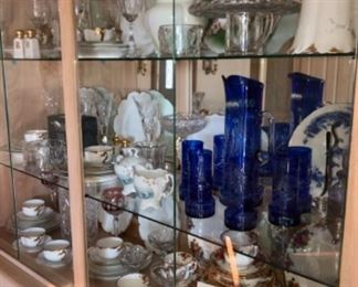 display space of a blond oak china cabinet display space, filled with antique glassware and china.