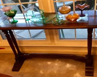 Antique Jacobean sofa table with carnival glass and green Victorian glass pieces.