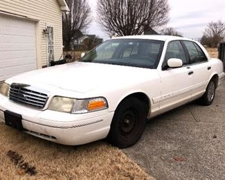 White Ford crown Victoria with new battery.  Engine attempts To start but appears to have a fuel issue.  Hub cap is in garage.