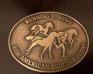 indian youth running with horses belt buckle