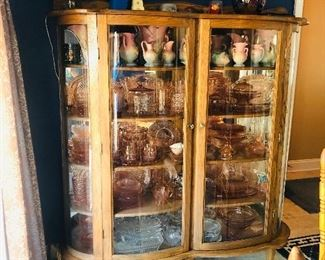 Double bow front oak china cabinet full of Hull and pink depression glass