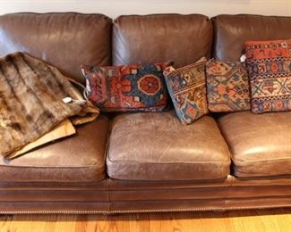Brown leather sofa shown with throw pillows made from antique hand knotted Oriental rugs and fur throw.