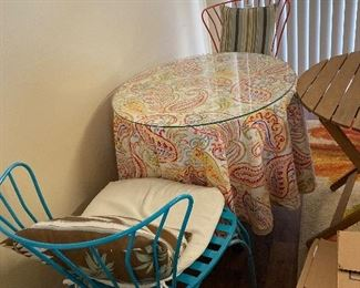 2 year old bohemian chairs and glass table. Partial picture of outdoor wooden table.