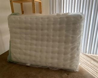 Brand new Queen Mattress with wooden shelving pictured behind the mattress.