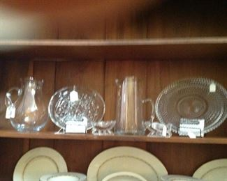 A couple of glass pitchers, platters and two cute glass sleighs