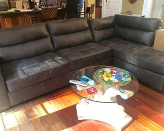 Faux leather sofa in perfect condition. Glass coffee table with base made of ice sculpture