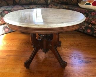 Marble top coffee table with base carved into the shape of a sweet dream