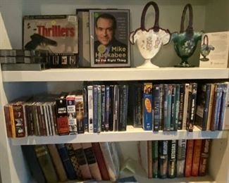 Two signed Fenton baskets, 1990's.  Antique books on the lower shelf. CD's, DVD's. Signed Mike Huckabee book.