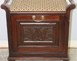 """Antique coal bin style magazine cabinet. Carved front panel folds forward for magazine storage.  Raised on small Cabriole feet.  Upholstered cushioned top creating a small bench. (23""""H x 21 1/2""""W x 14""""D)"""