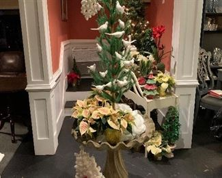 An antique birdbath holds miniature poinsettias and the white dove Christmas tree
