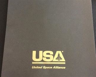 """United Space Alliance Commemorative Package for the successful completion of the NASA Space Shuttle Program. Package includes Commemorative Book that examines the accomplishments of the Space Shuttle Program, Commemorative Video,  and a matted """"End of Space Shuttle Program"""" suitable for framing. Enclosed in an embossed slip case."""