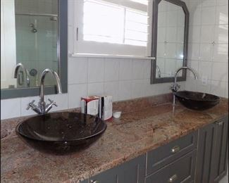 Bathroom Vanity with Double Glass Sinks and Granite Top.