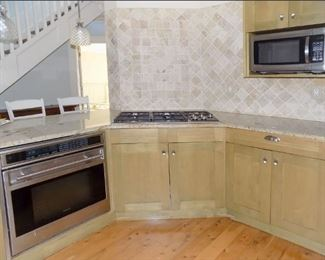 Wolf Oven and Gas Cooktop.  Cabinets with Granite Tops.  Pendant Lamps.  Magic Chef Microwave.