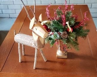 Carved reindeer with Christmas arrangement on craftsman style coffee table