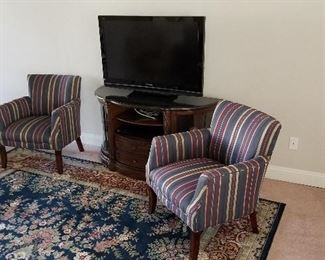Very nice chairs and Panasonic flat-screen on top of a gorgeous round glass entertainment center