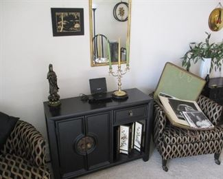 pair of upholstered armchairs. Black storage cabinet