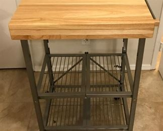 """Utility Folding Kitchen Cart  Create an instant island for yourself with our Utility Kitchen Cart. This versatile cart is made of rubber wood and a sturdy steel frame featuring four caster wheels that easily rolls to wherever you need it. It also provides a built-in prep surface with two additional shelves for easy storing and transport and folds to just 6"""" wide so it can easily be store neatly away when not in use. Weight capacity is 100 pounds for the top shelf and 50 pounds for middle and bottom shelves.  * Prep-surface is made of rubber wood * Two shelves provide additional storage * Casters provide an instant, mobile island * Folds to just 6"""" depth when not in use"""