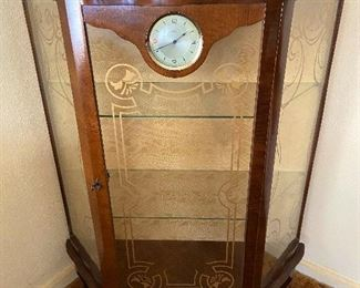 Small china cabinet with built in clock.