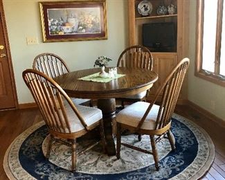 Round oak table and  4 curved back chairs.  Round polyester rug, corner cabinet is built in and not for sale.