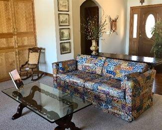 Ethan Allen multicolored sofa, glass top coffee table, cane Victorian rocker