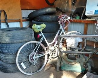 Lawn mowers, bicycles, tires, in one of the sheds