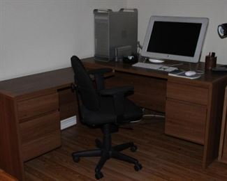 "Laminated Oak ""L"" Shape Desk with Small Upper & Lower File Drawers.  Shown with Apple Computer: Tower, Monitor, Keyboard and Mouse.  Also shown is  Black Swivel Desk Arm Chair"