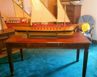Large, hand carved wooden ship model by the late local artist Kenneth Floyd. Extremely detailed.  Large single drawer table.