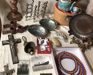 Eclectic collectibles: Metal crucifixes, photo postcards, Persian brass bell, Russian angel ornaments, wooden nutcrackers, gilt metal candle stand, stacking chrome tripod candle holders by Nagel, abalone shells, fossils, Chinese tea set in basket, African (?) beaded collars, copper tray