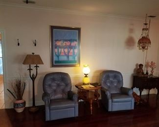 Pair of blue Lazy boy leather recliners, parrot floor lamp, antique hanging crystal pink to clear lamp. Buddha statue, pottery.