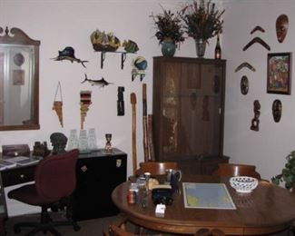 """Office full of eclectic art, carvings, masks, fish and more. Nice table and captain chairs set. Corner desk, very """"Beachy"""" looking Ethan Allen"""