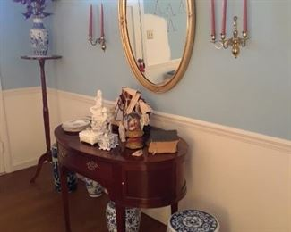Oval hall chest, pedestal, Chinese garden seat, oval mirror, brass wall sconces, blue and white Oriental vases