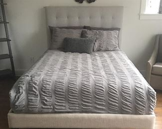 West Elm queen sized bed and fabric headboard.