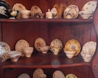 Tea cup collection in a pine corner cabinet.