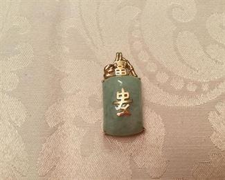 "Jade pendant light green with Chinese's writing in gold 14kt gold & bail. 2""T"