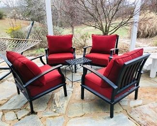 Four metal chairs with red cushions, black metal table