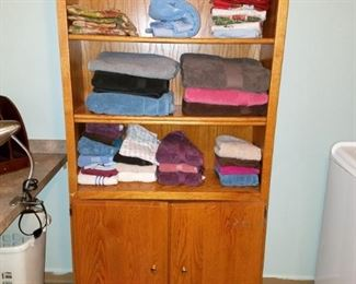 Bath linens. tall wood bookcase/cabinet