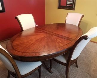 Gorgeous oval dining room table accompanied with four ivory upholstered chairs
