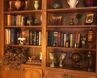 Books, brass, and a variety of decor including McCoy and Roseville