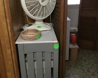 A small cabinet with drawers.  Lots of fans in this house.