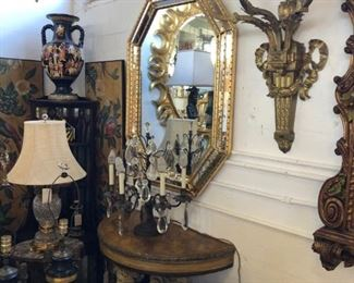 Pair of octagonal giltwood Italian mirrors, opposing pair of 18th century demilune consoles with figural putti, pair of oversized bronze sconces