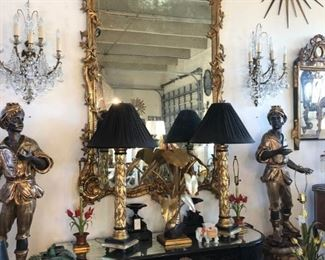 Giltwood mirror of grand scale, pair of giltwood figural blackamoors, pair of sunburst mirrors, pair of foliate giltwood table lamps, English lacquer console with inset mirrored top, pair of fine French bronze and crystal sconces, burnt bamboo settee.