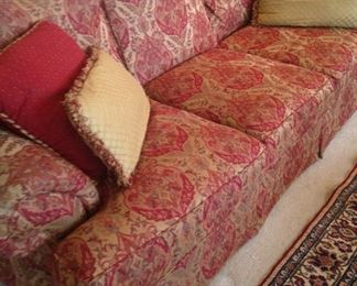 One of two matching sofas in red and gold