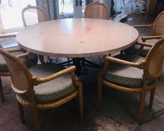 designer round  dining table  with six chairs--Table has a wrought iron pedestal  bottom