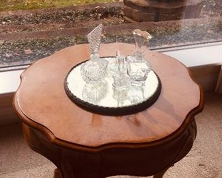 round  table with a mirrored plateau and fine perfume bottles