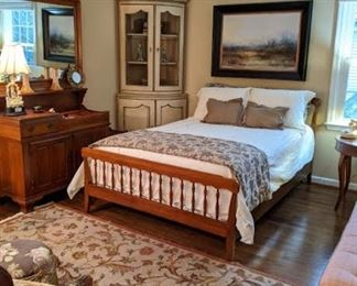 Full size cherry bed, with Sferra linens, matching cherry dry sink and wall mirror, handwoven flat-weave Persian Tabriz design rug and vintage 2-piece French country corner cabinet, with wire mesh doors.