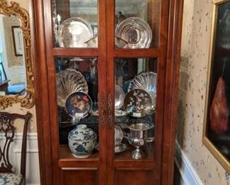 One of the pair of Century Furniture lighted china cabinets, with beveled glass door and side lights.