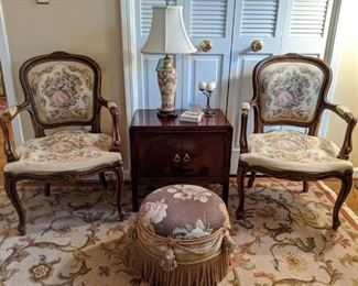 Pair of French bergere chairs, with tapestry fabric, vintage mahogany 2-door chest, Asian porcelain table lamp, w/shade & finial and custom made ottoman, with French braid and metal bees.